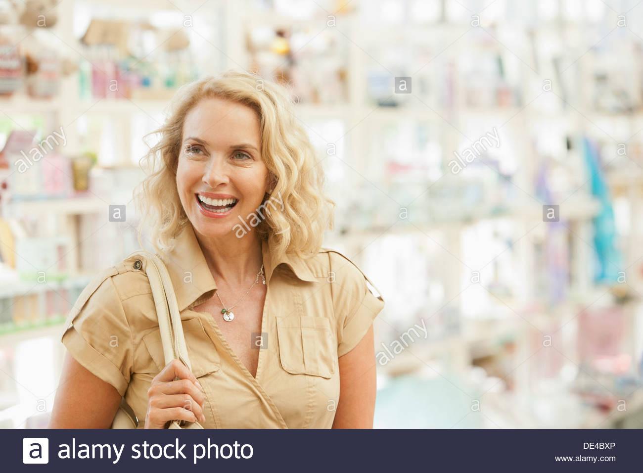 Lächelnde Frau shoppen im Shop Stockbild