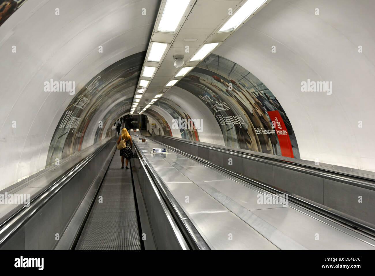 Frau auf travelator, die Fahrbahn im Tunnel zur U-Bahn, Plattform London England Großbritannien Stockbild