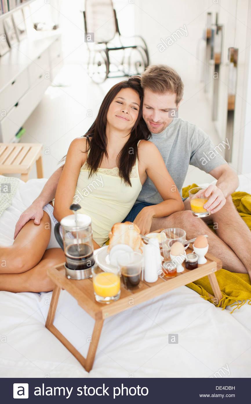 Brautpaar mit Frühstück im Bett Stockbild