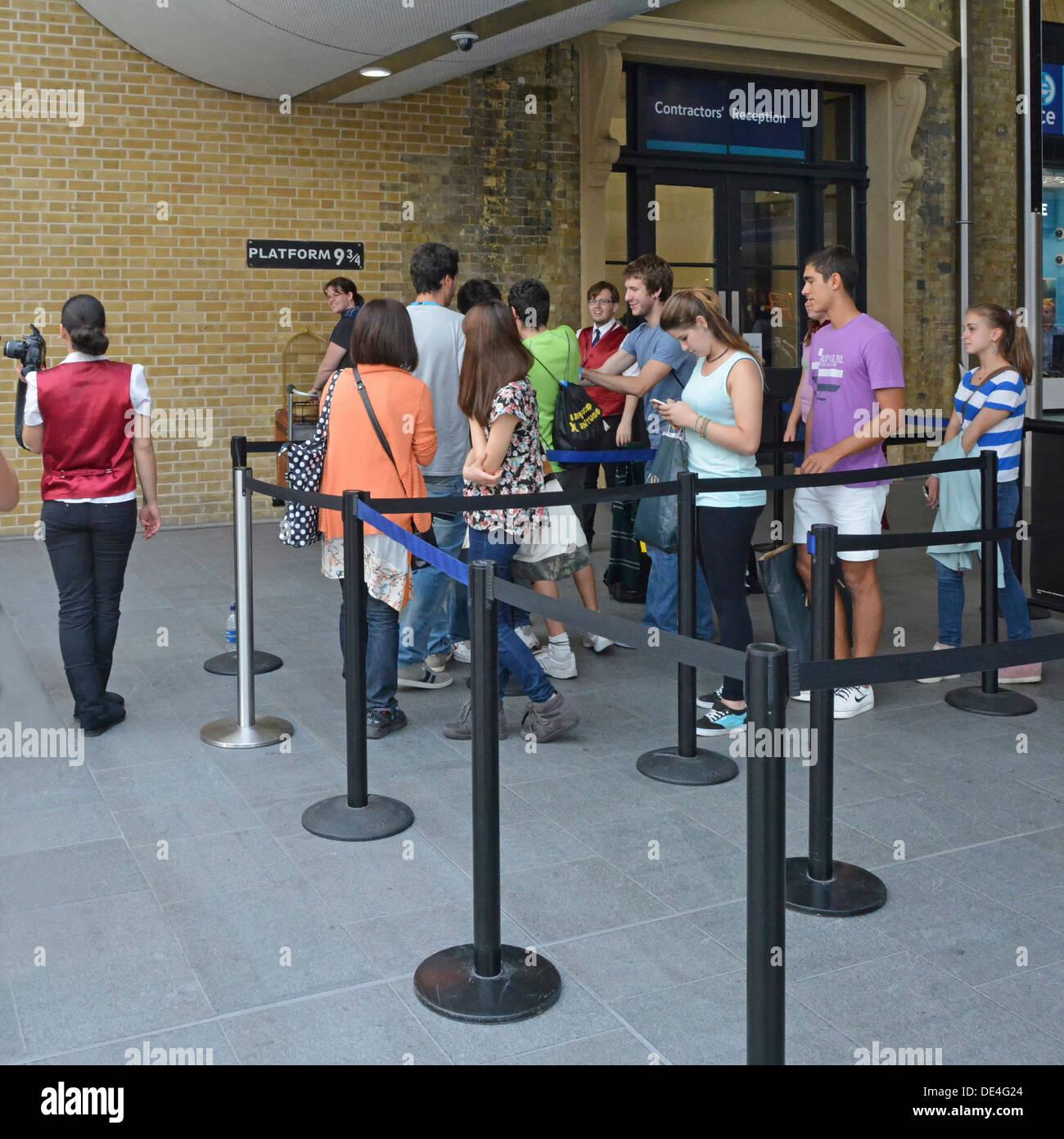 Fans, die Schlange, um ein Foto auf der Plattform neun und drei Viertel Zeichen von Harry Potter-Geschichte an der Kings Cross station Stockbild