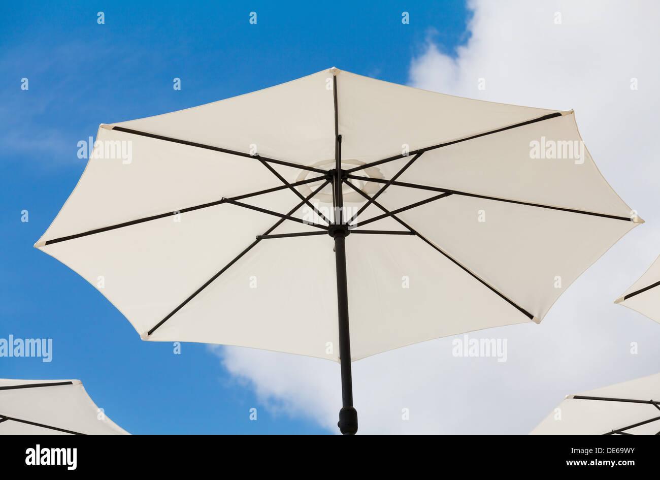 Weiße Sonnenschirme auf klaren blauen Himmel Stockbild
