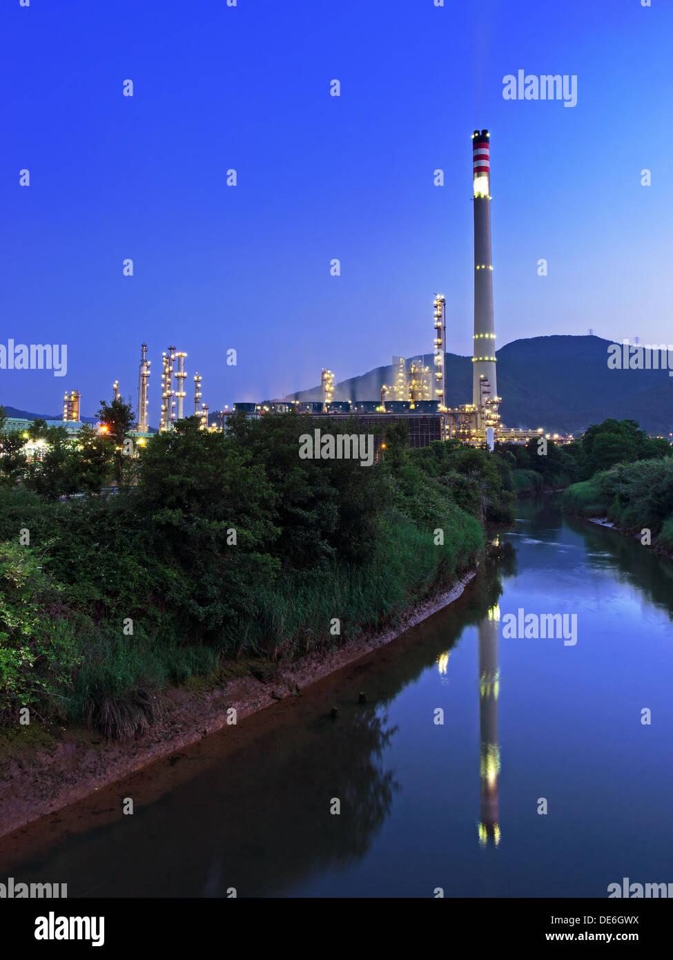 industrielle Raffinerie mit Schornstein in der Nähe eines Flusses Stockbild