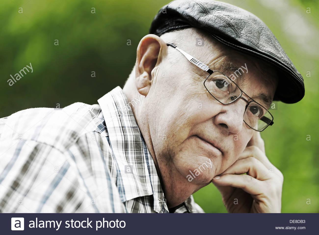 Deutschland, Nordrhein-Westfalen, Köln, Senior Mann mit Mütze und Brille im Park, Nahaufnahme Stockfoto