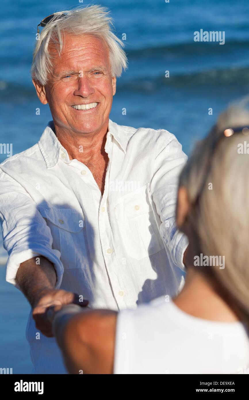 Glücklich senior Mann und Frau zu zweit tanzen und halten die Hände auf einem einsamen tropischen Strand mit blaue Stockfoto