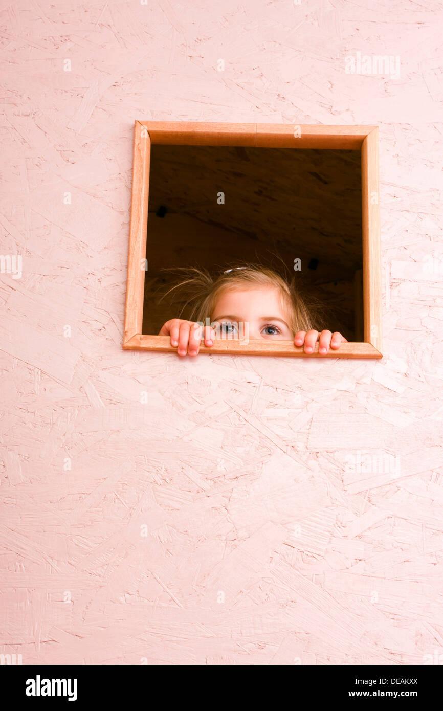 Mädchen, 3 Jahre, Blick durch Fenster Stockfoto