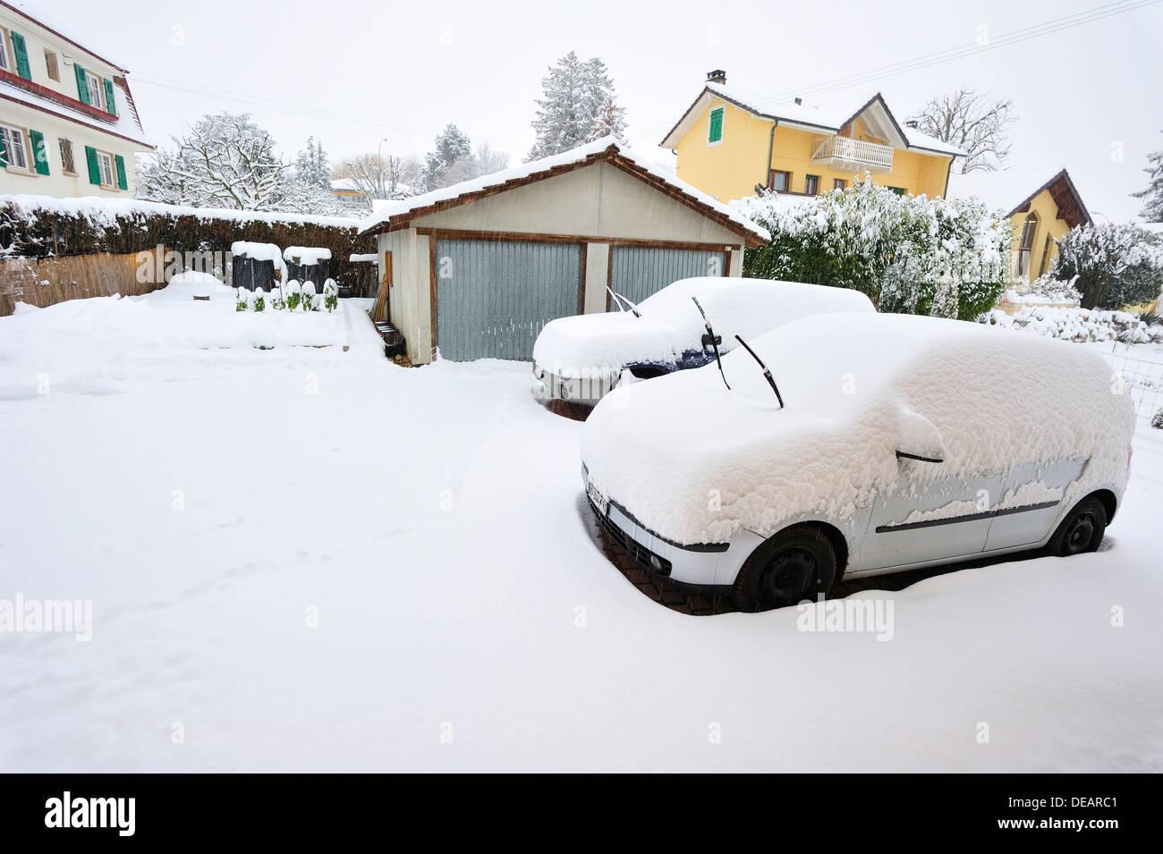 Schnee-Szene. Zwei geparkte Autos von Schnee bedeckt werden. Sie sind nicht in der Garage (im Hintergrund) Stockbild