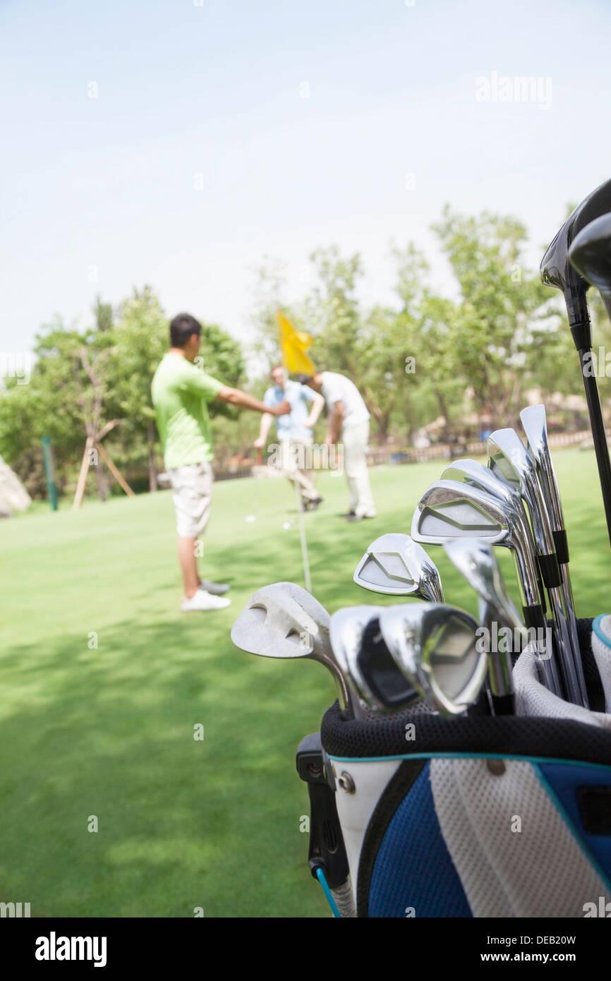 drei freunde spielen golf auf dem golfplatz im fokus des. Black Bedroom Furniture Sets. Home Design Ideas