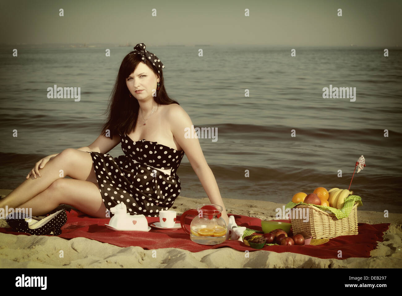 picknick im gr nen sch ne frau sitzen auf roten decke am sandstrand retro stil stockfoto bild. Black Bedroom Furniture Sets. Home Design Ideas
