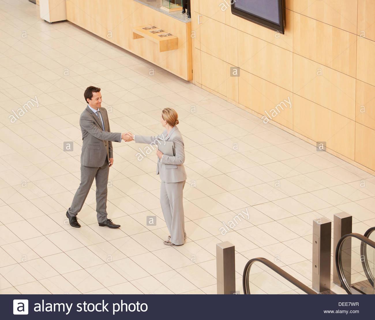 Geschäftsleute, die am Ende der Rolltreppe stehen Stockbild