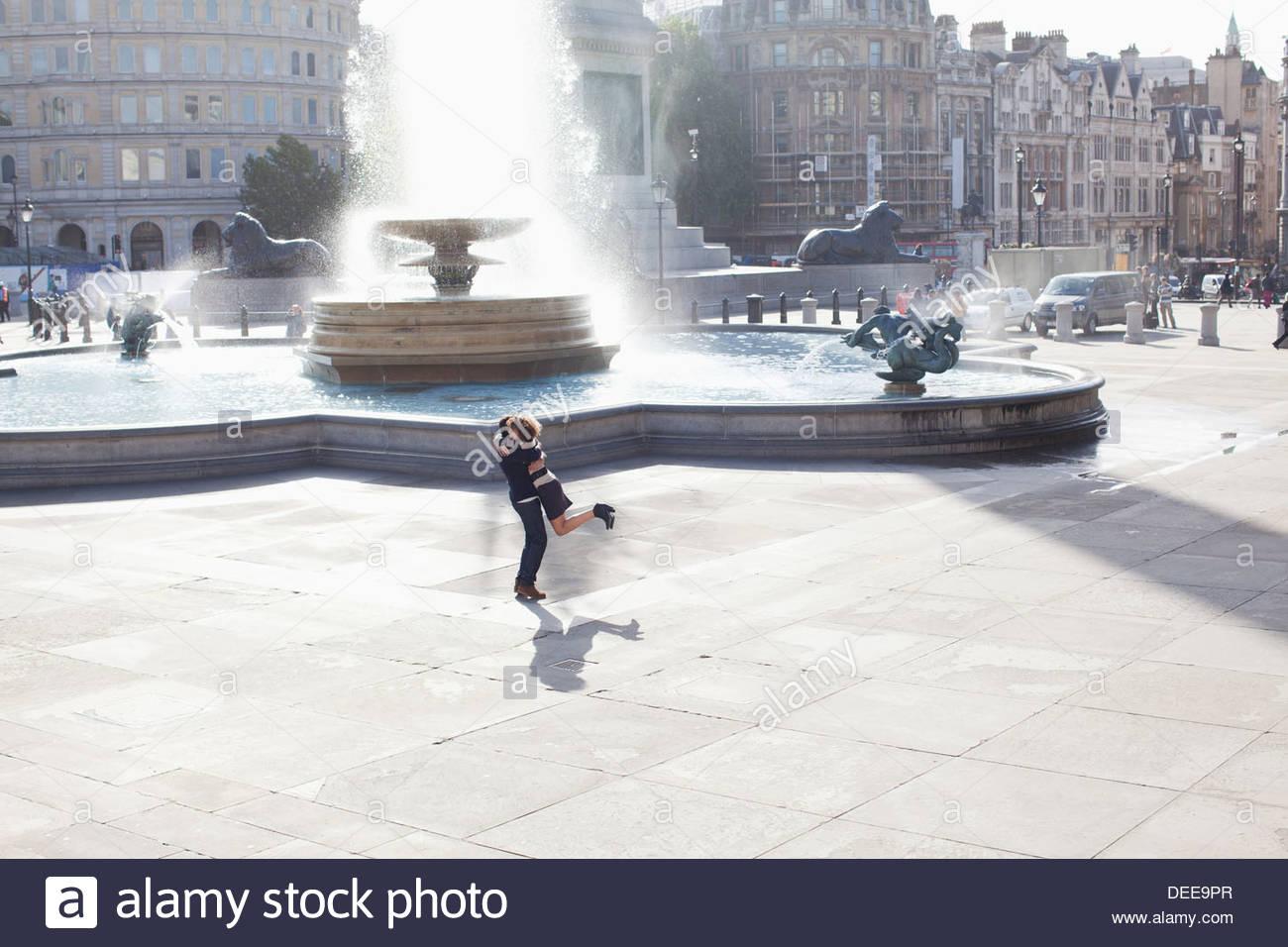 Mann heben Frau vor städtischen Brunnen Stockbild