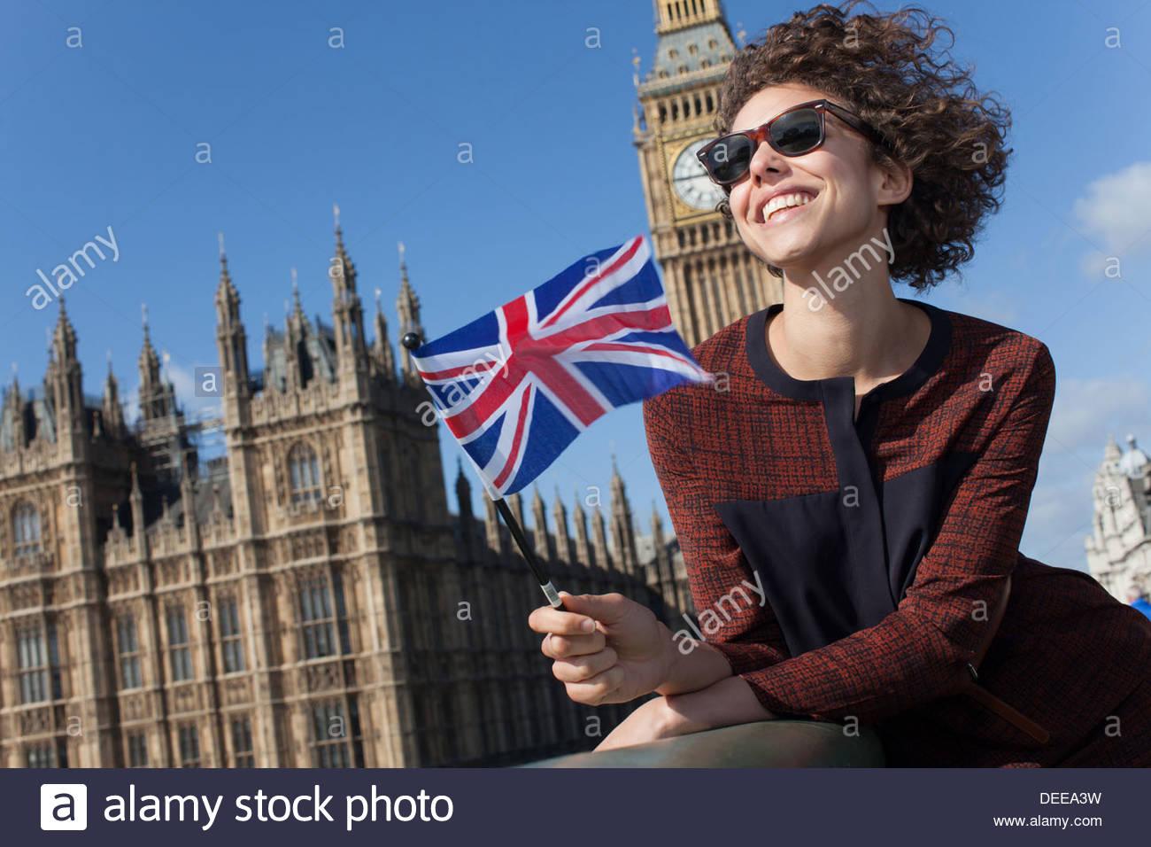 Portrait von lächelnden Frau mit britischer Flagge vor Big Ben clocktower Stockbild