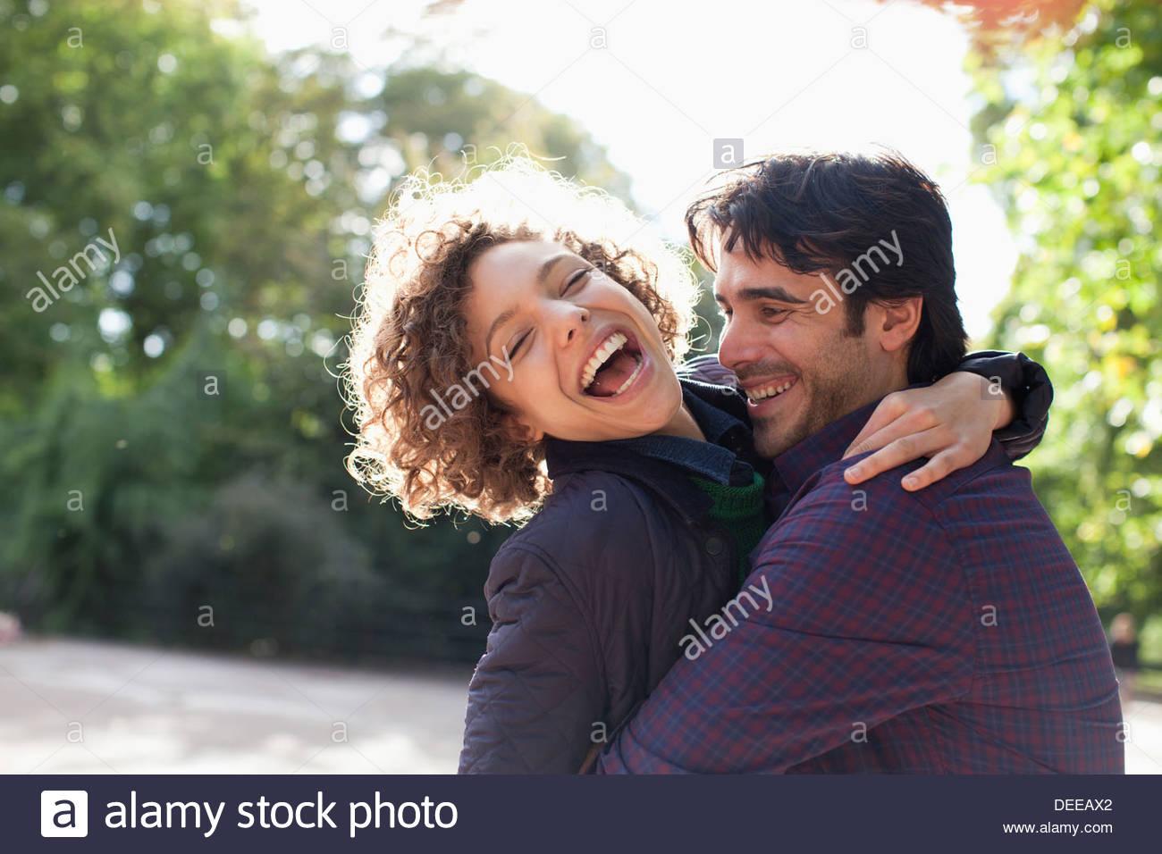 Sonne hinter glückliches Paar umarmt Stockbild