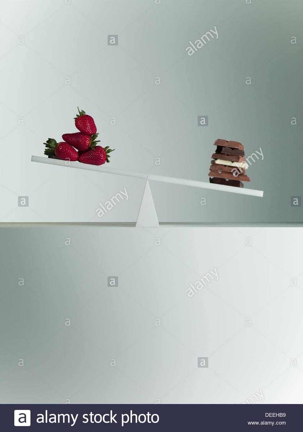 Schokoriegel, Kipp-Wippe mit Erdbeeren am gegenüberliegenden Ende Stockbild
