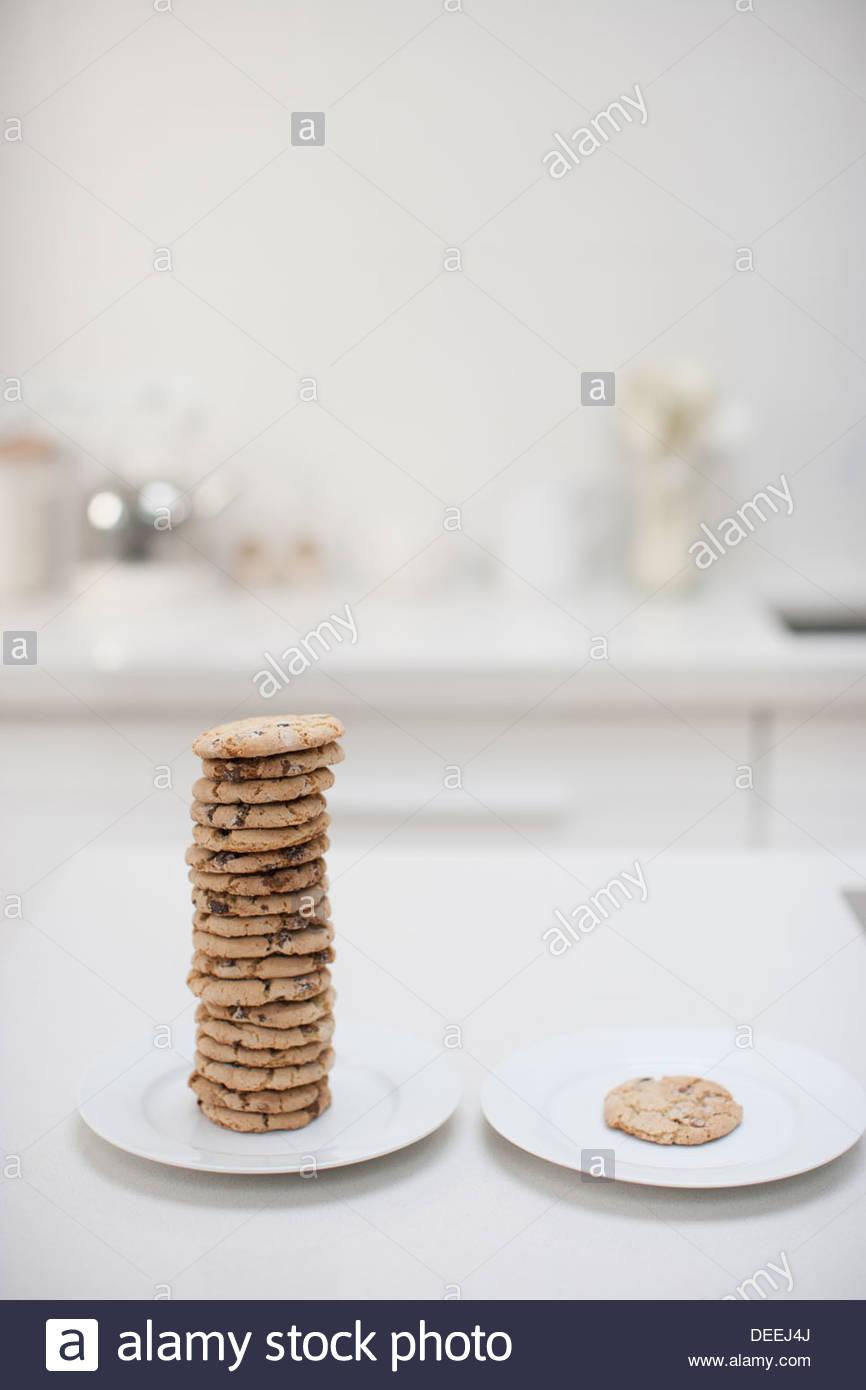 Stapel von Cookies auf Platte neben einzelnen Cookie auf Platte Stockbild