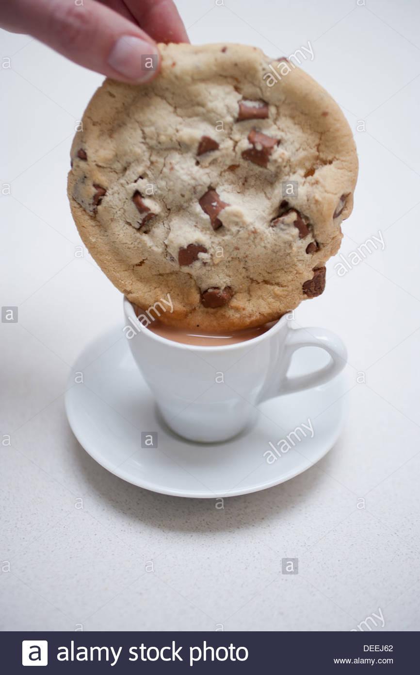 Hand, die große mit Schokosplittern in kleine Kaffeetasse eintauchen Stockbild