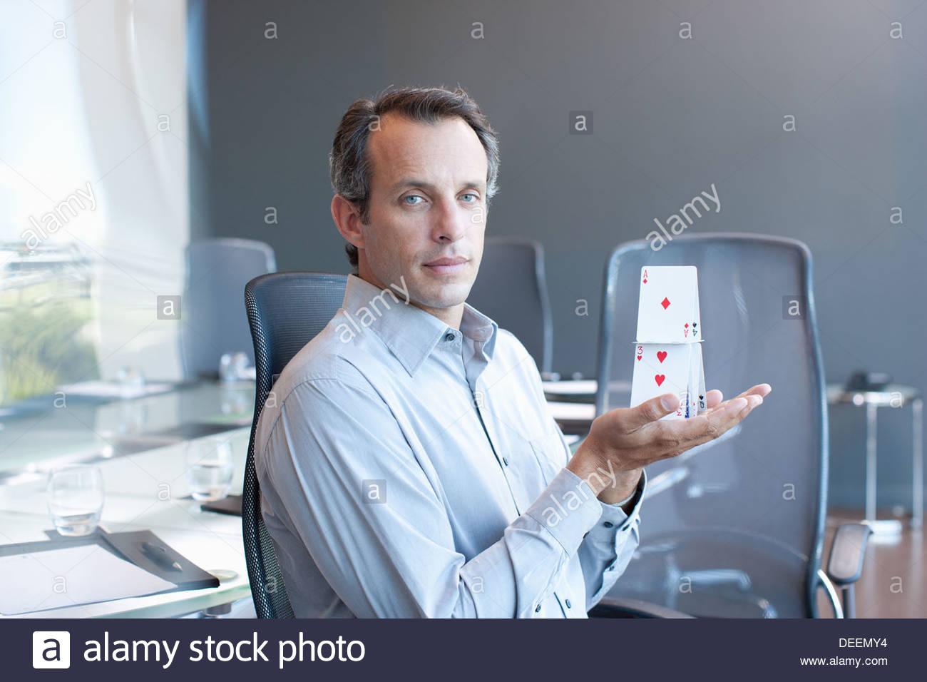 Geschäftsmann hält Kartenhaus im Konferenzraum Stockbild