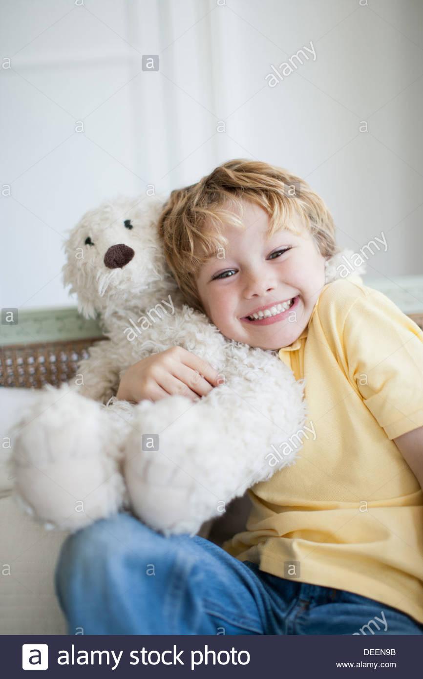 Lächelnde junge umarmt Teddybär Stockbild