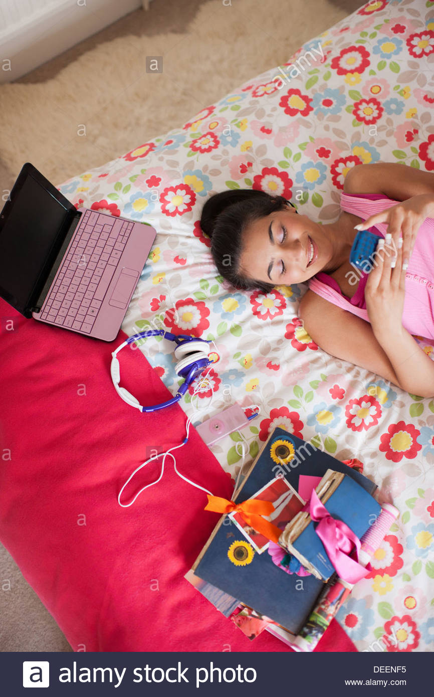 Teenager-Mädchen Handauflegen Bett SMS auf Handy Stockbild