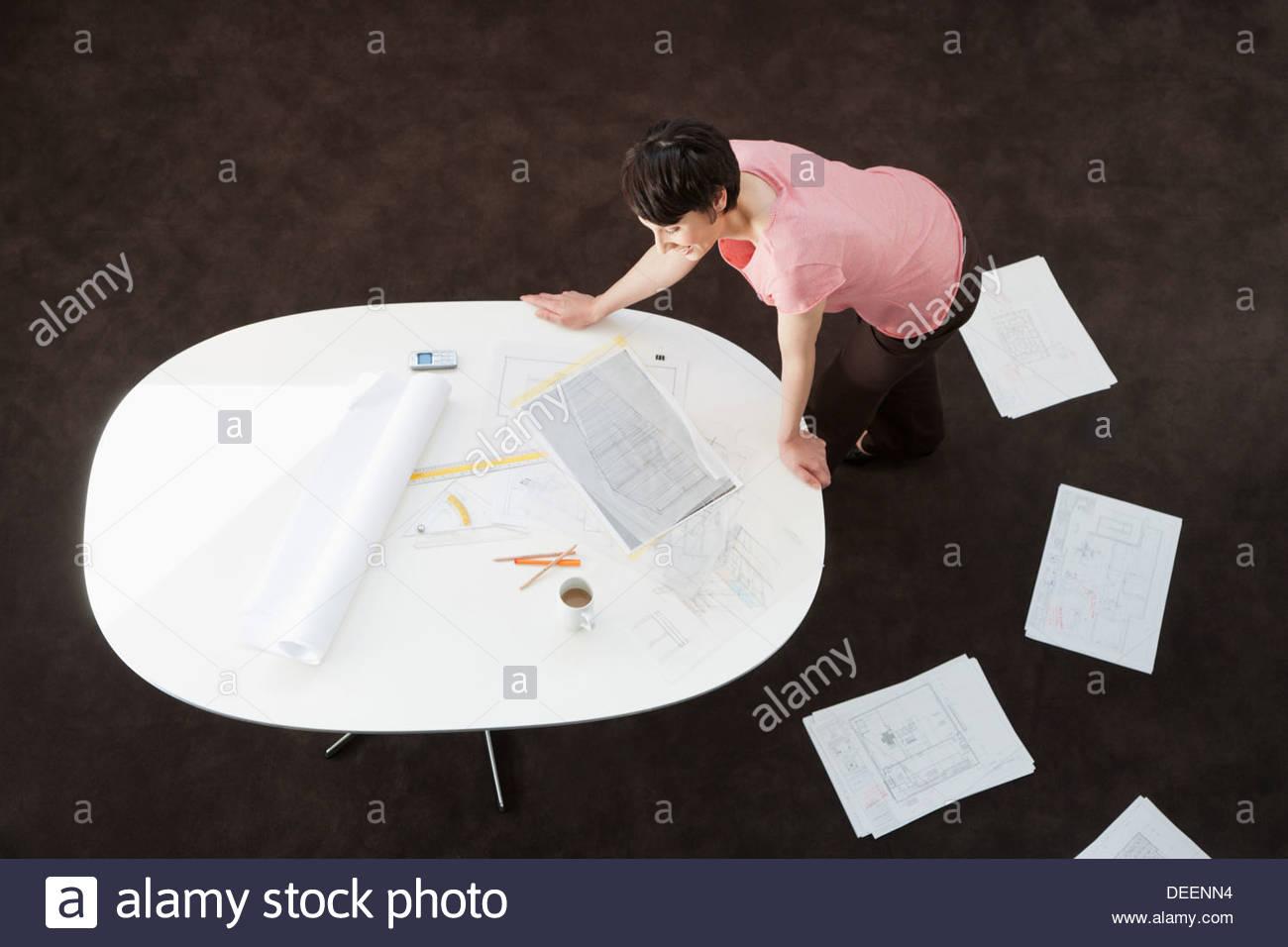 Geschäftsfrau, die Entwürfe zu betrachten, auf einem Tisch Stockbild
