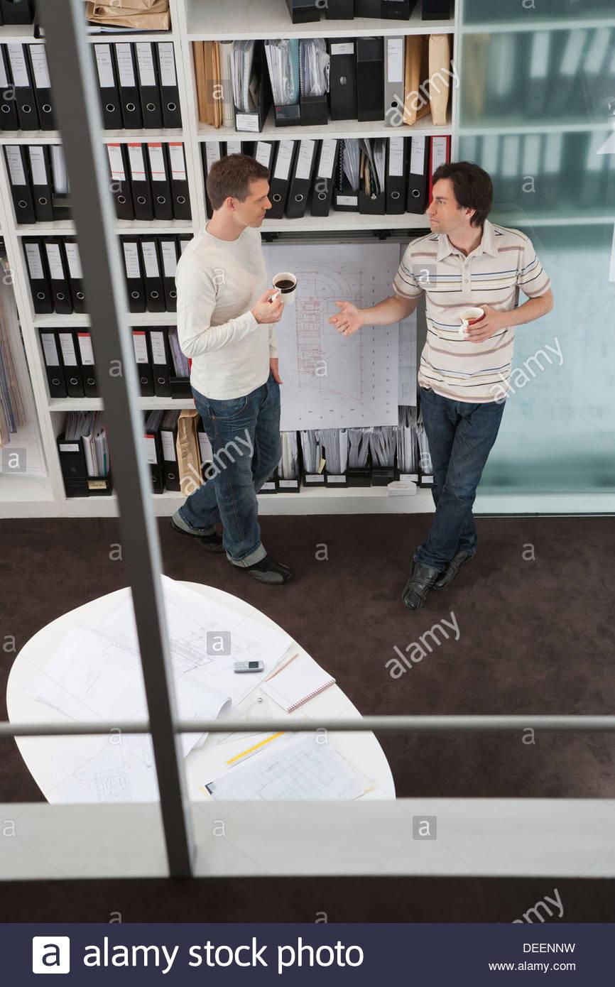Zwei Geschäftsleute halten Kaffee im Büro Stockbild