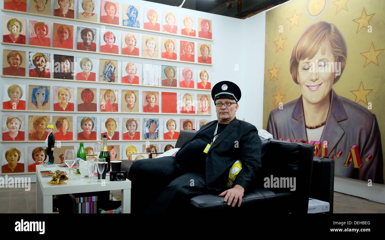 Kurator und Künstler Konstantin Schneider sitzt vor Kunstwerken mit Bundeskanzlerin Merkel am Kraftwerk in Berlin, Stockfoto
