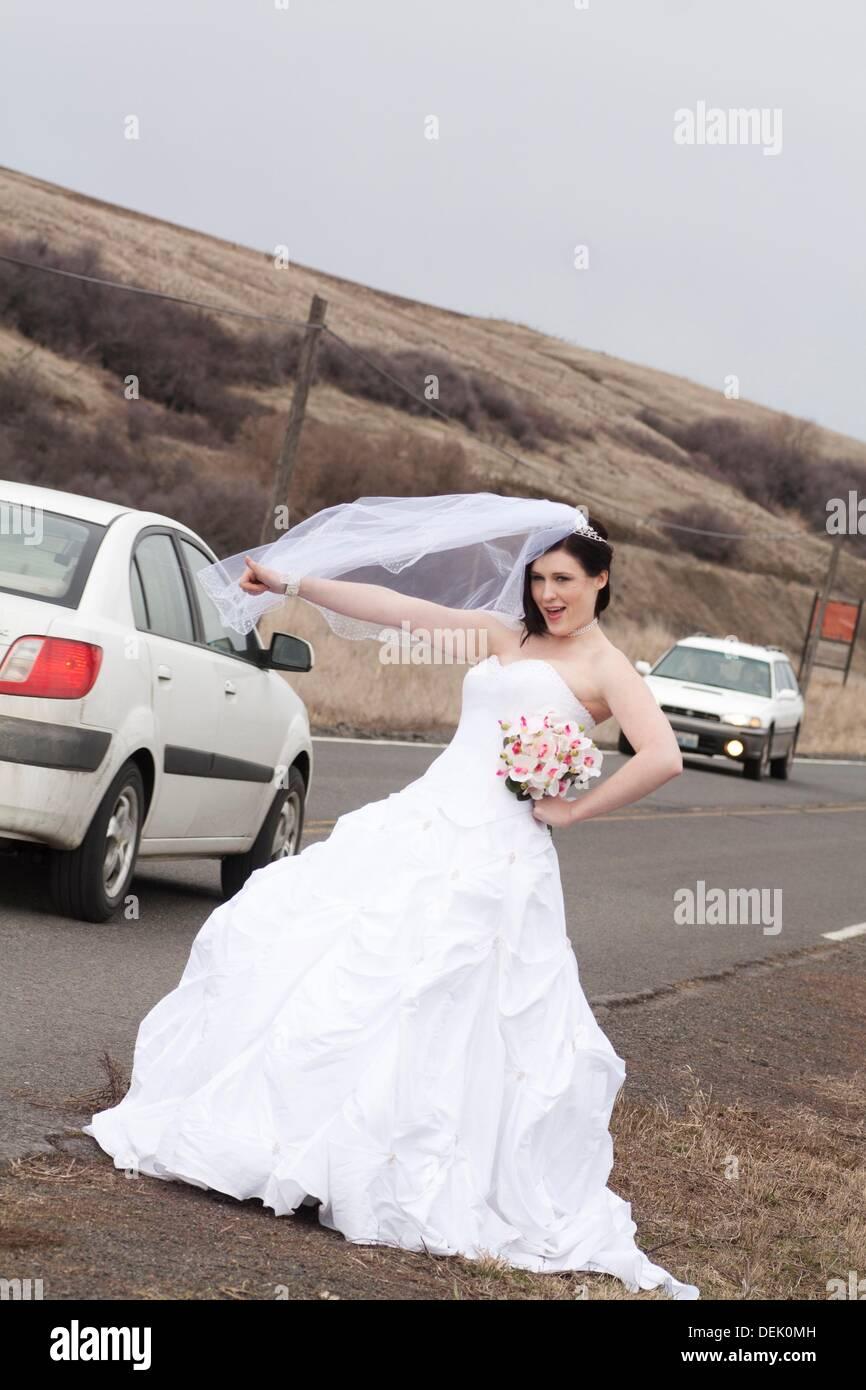 Eine junge Frau im Brautkleid, per Anhalter auf einer Landstraße in ...