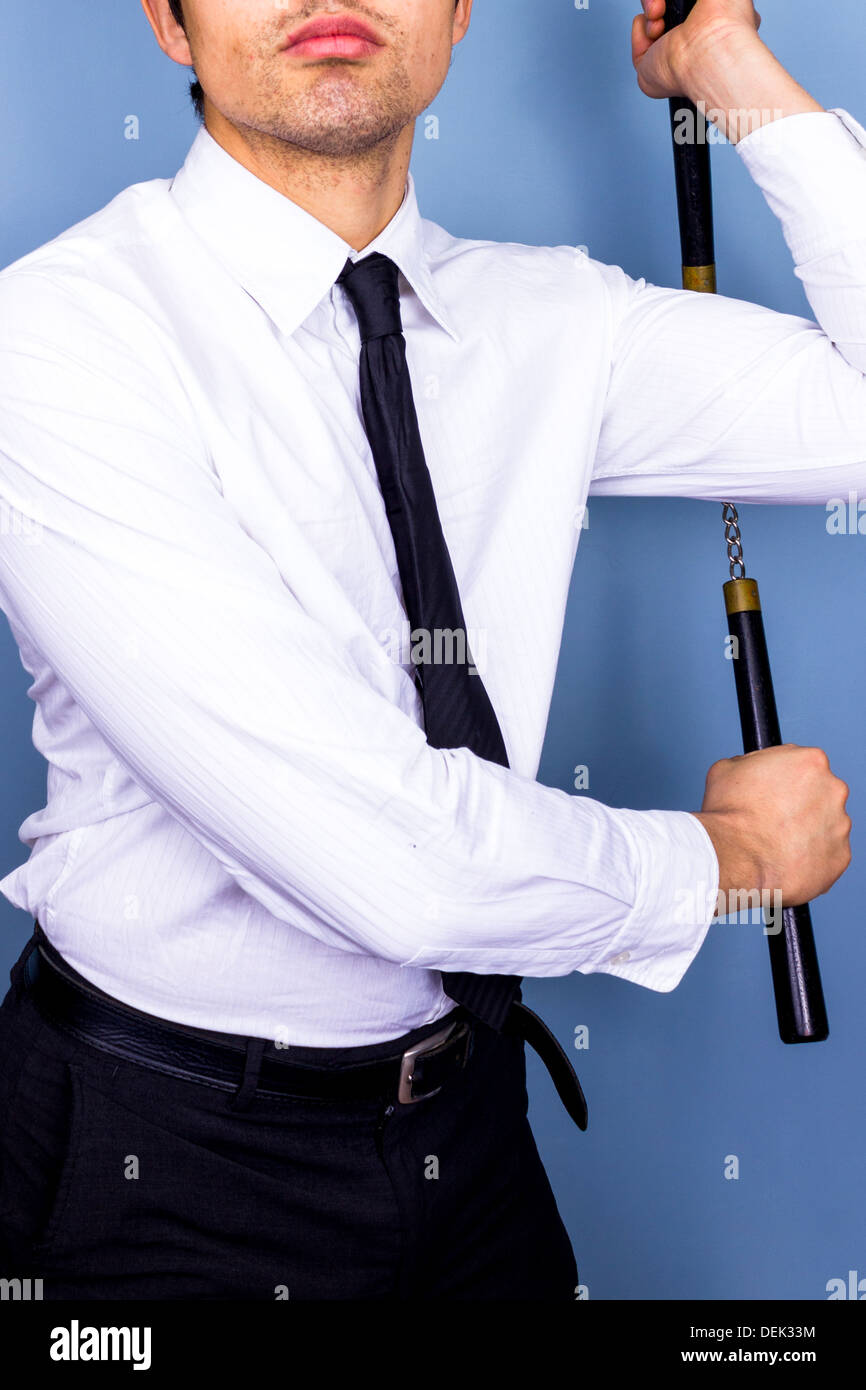 Geschäftsmann winkt ein paar Nunchucks um Stockbild