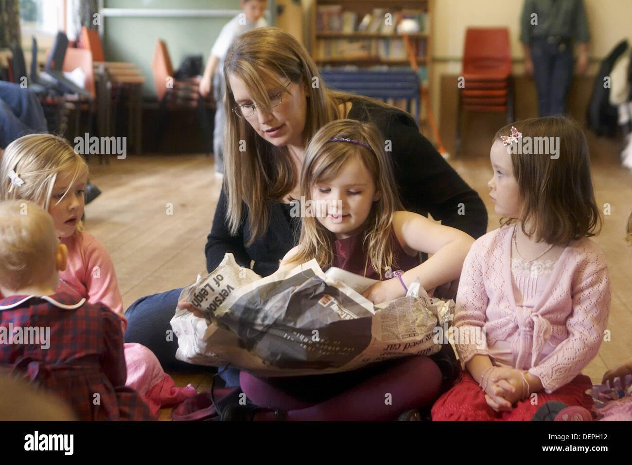 4 Jahre altes Mädchen bei einer Kinderparty öffnen ein Geschenk im ...