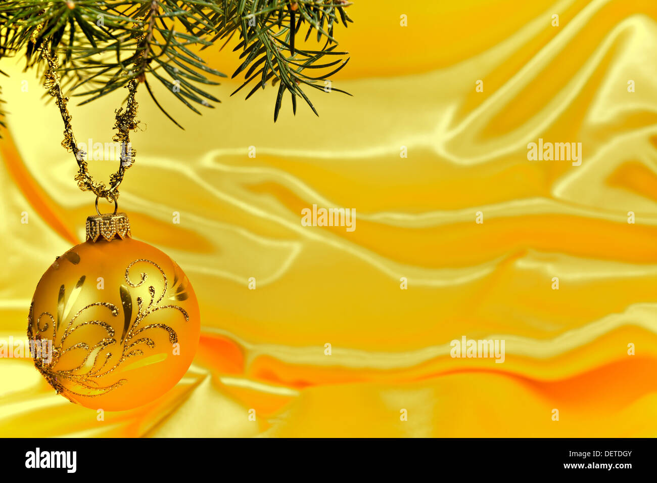 Ball und Kiefer Baum Zweig Weihnachtsdekoration auf gelber Seide Stockbild