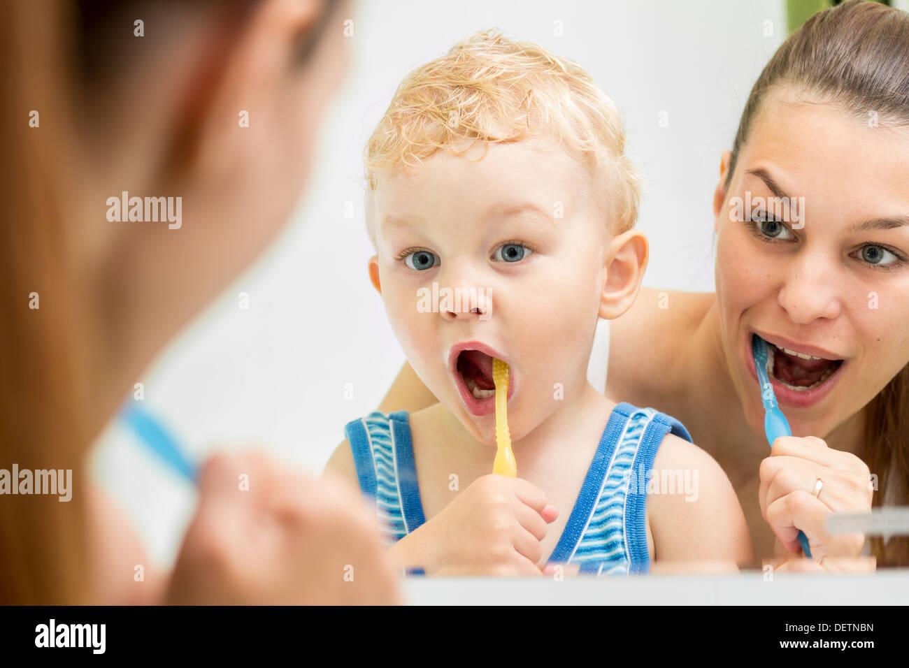 Mutter lehrt Kinder Zähne putzen Stockbild