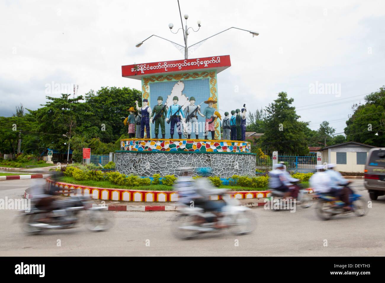 Leute fahren von Statuen an einem Kreisverkehr in Mawlamyine. Stockbild