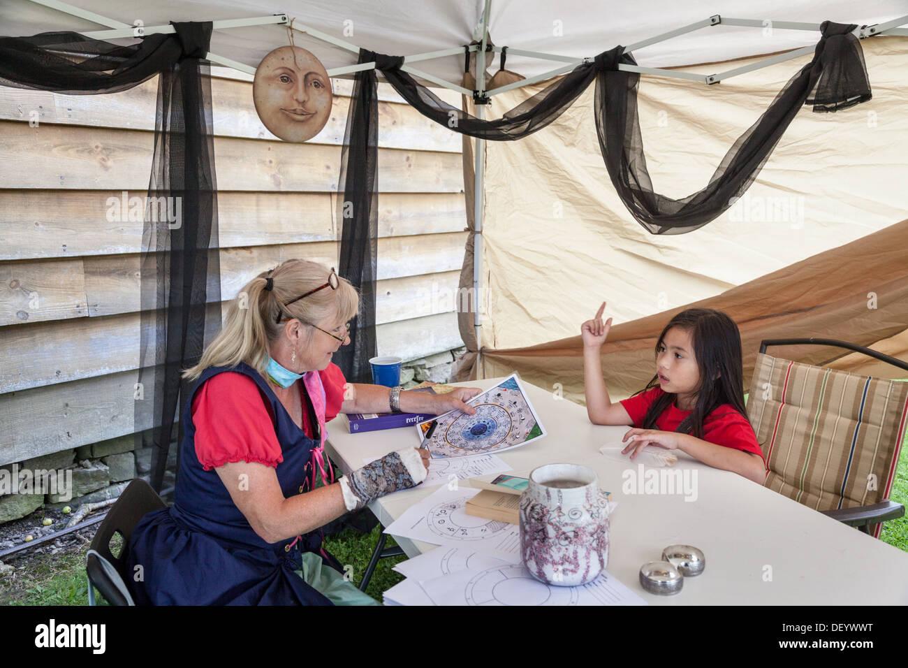 Wahrsagerin Horoskop von kleinen Mädchen zu lesen. Mittelalterliches Festival, Bundesstaat New York, Montgomery County Stockbild