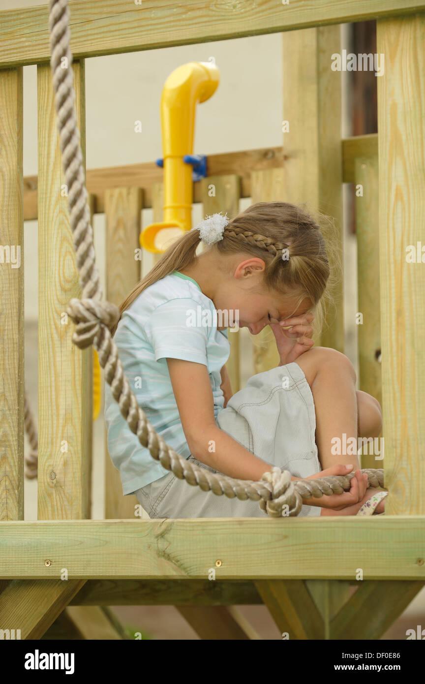 7-Jahr-altes Mädchen weinen, verletzt ihr Fuß ein Kletterseil auf einem Spielplatz Stockfoto