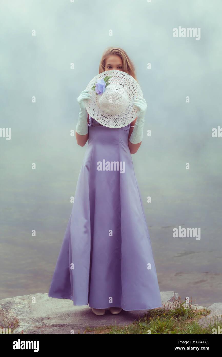 eine schöne junge Frau verbirgt sich hinter einer weißen Sonnenhut Stockbild