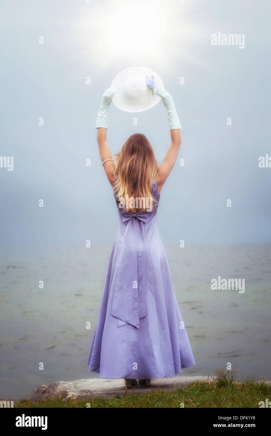 eine Frau in einem lila Kleid steht an einem See mit einem Sonnenhut Stockbild