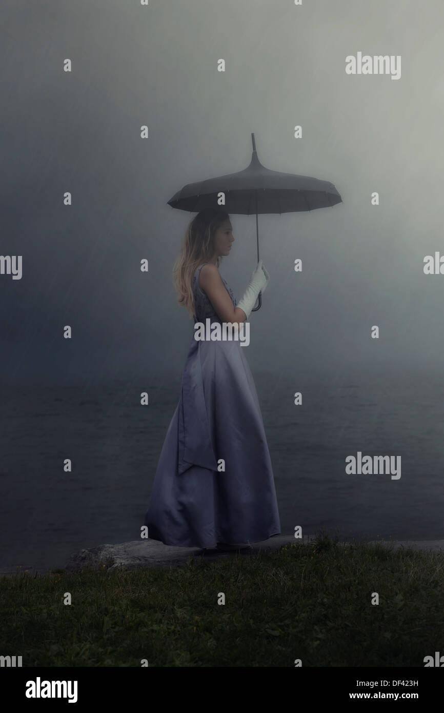 eine Frau in einem lila Kleid steht an einem See mit einem schwarzen Schirm im Regen Stockbild
