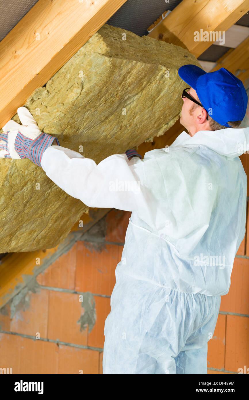 Arbeitnehmer insgesamt setzt das Dach thermisches isolierendes Material mit Handschuhen Stockbild