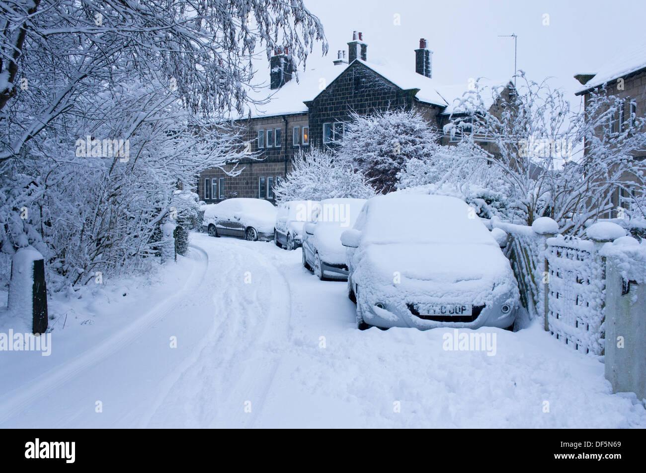 Winter Szene mit parkenden Autos außerhalb Doppelhaushälfte in einer ruhigen Wohnstraße, alle im Vertrag von frischem Schnee - Guiseley, England, UK. Stockbild