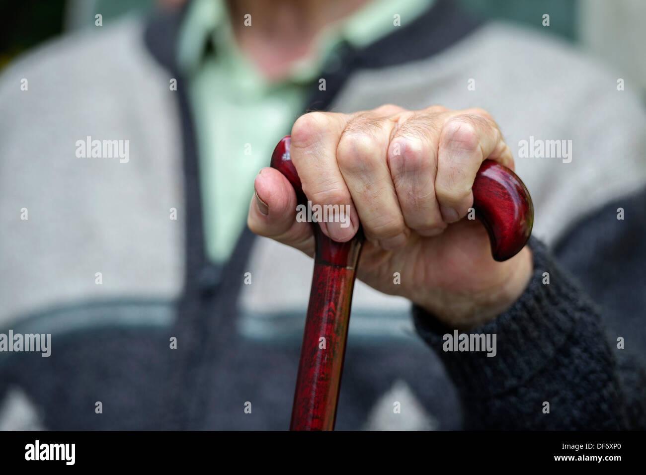 Eine ältere Rentner sitzt mit seinen Händen auf einen Spazierstock in einem Pflegeheim. Stockbild
