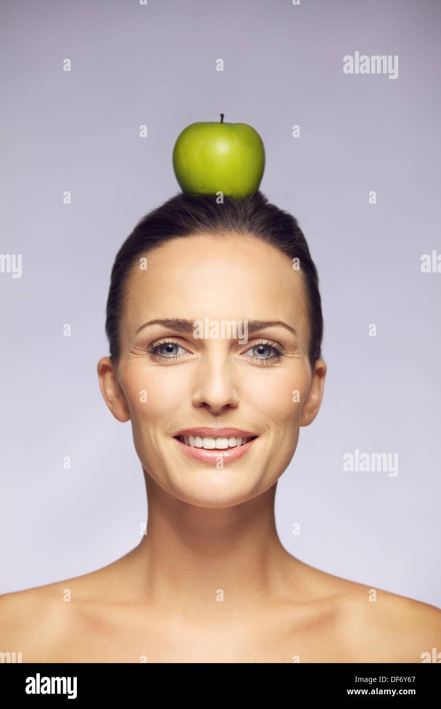 Porträt einer schönen jungen Frau Ausgleich eines grünen Apfels auf Kopf vor grauem Hintergrund isoliert. Stockbild