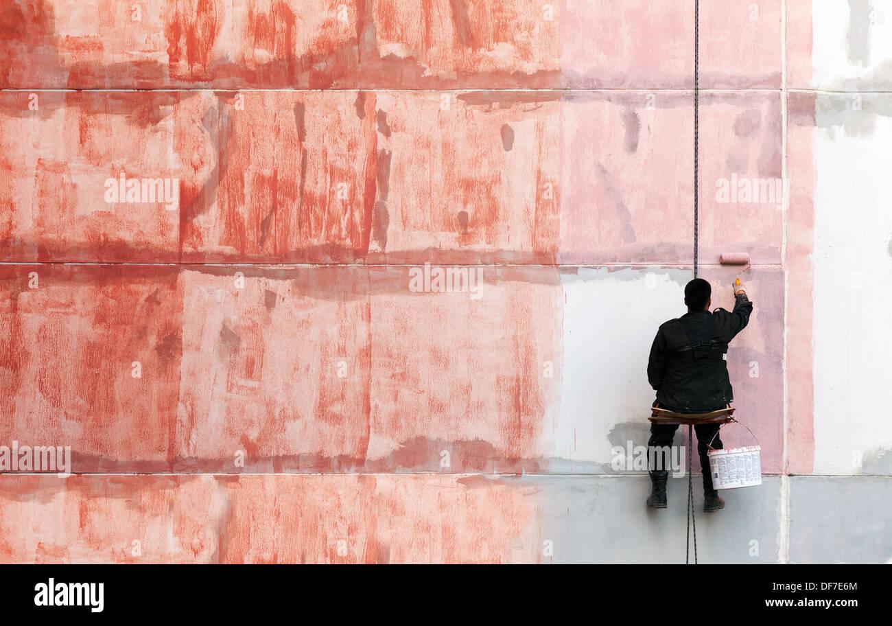 maler arbeitet an der äußeren gebäudewand mit roter grundierung