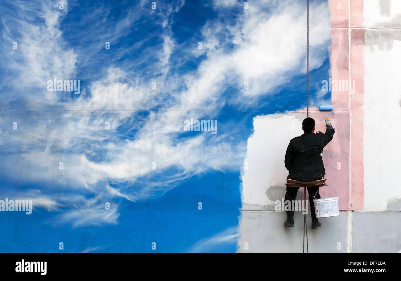 Maler malt strahlend blauen Himmel an der städtischen Wand Stockbild