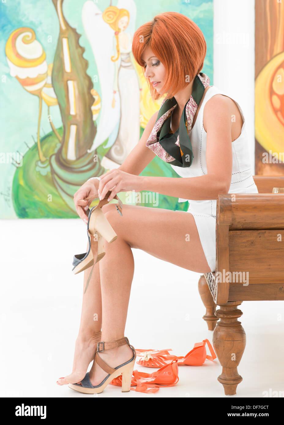 Seitenansicht der junge schöne rothaarige Frau sitzt auf einer Holzbank, die ihre Schuhe mit bunten Bildern auf Hintergrund ändern Stockbild