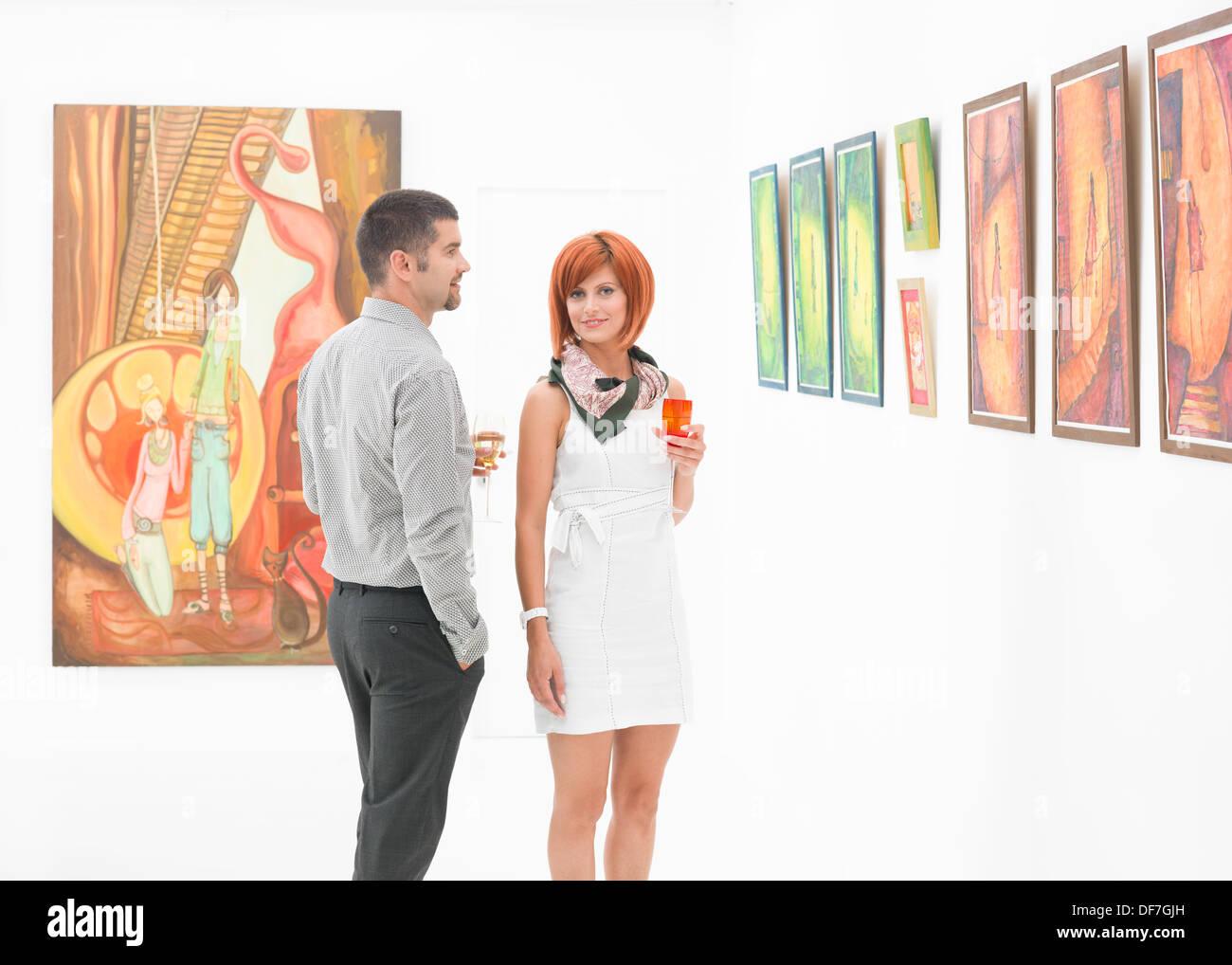 junge schöne Frau posiert neben einem kaukasischen Mann in einer Kunstgalerie, bunte Gläser Wein in ihren Händen halten Stockbild