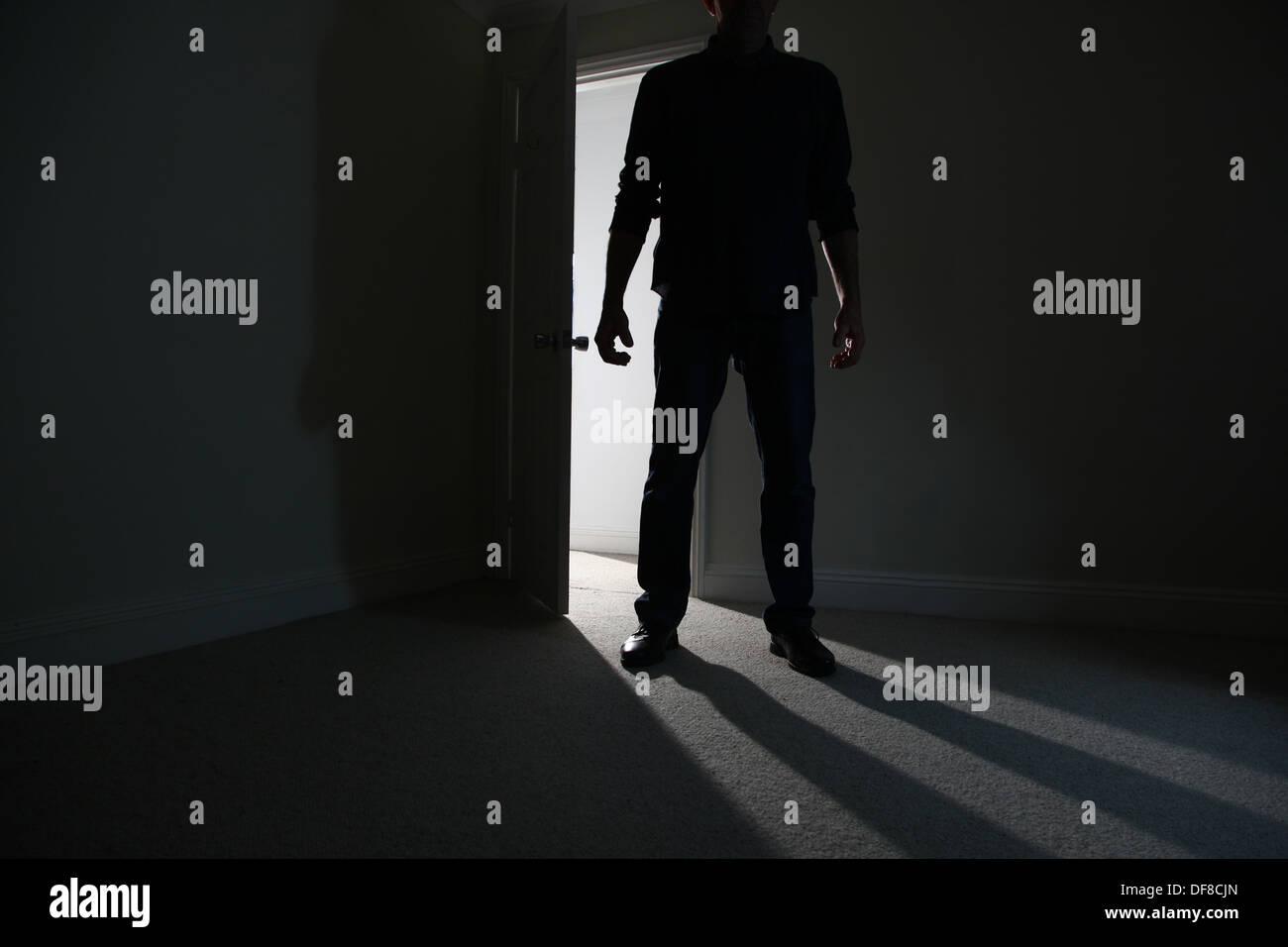Silhouette eines männlichen Erwachsenen in einer offenen Tür stehe, in einen dunklen Raum. Modell veröffentlicht Stockbild