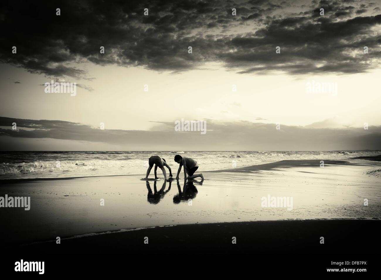 Kinder spielen am Strand Stockbild
