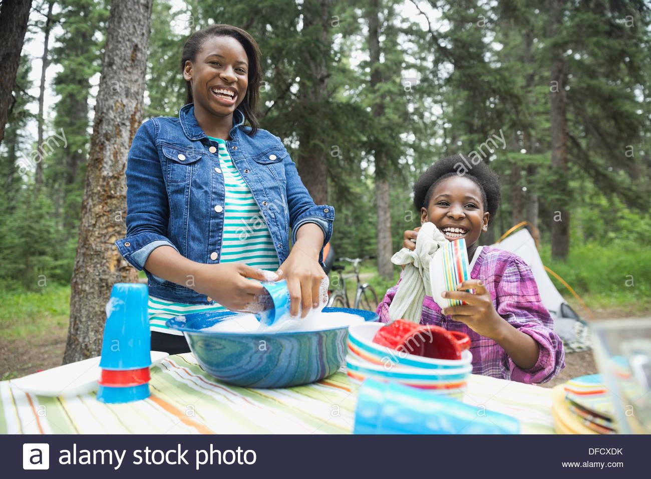 Glücklich Schwestern beim Abwasch auf Campingplatz Stockbild