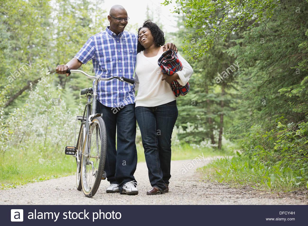 Fröhliches paar mit dem Fahrrad, zu Fuß auf den Weg Stockbild