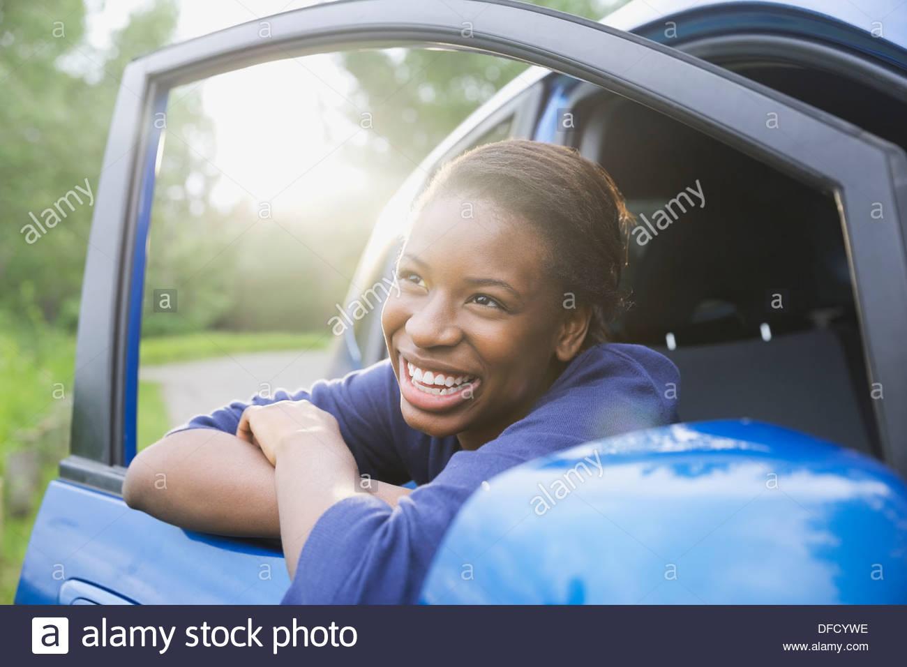 Fröhliche Teenager-Mädchen, stützte sich auf Autotür Stockbild
