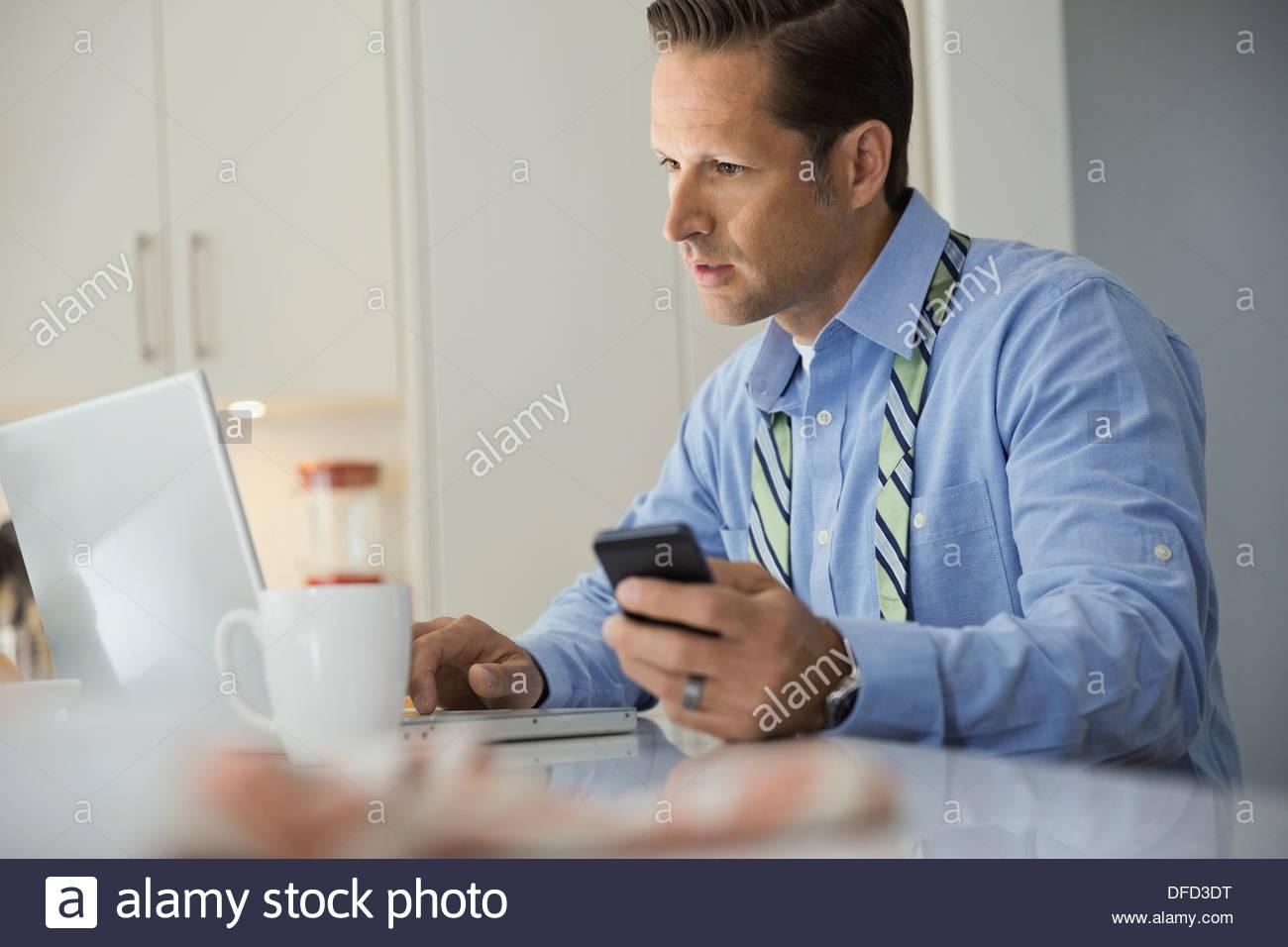 Reife Geschäftsmann mit Laptop in der heimischen Küche Stockbild